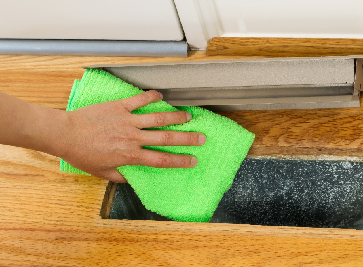 Cleaning ducted floor heater with green microfiber cloth