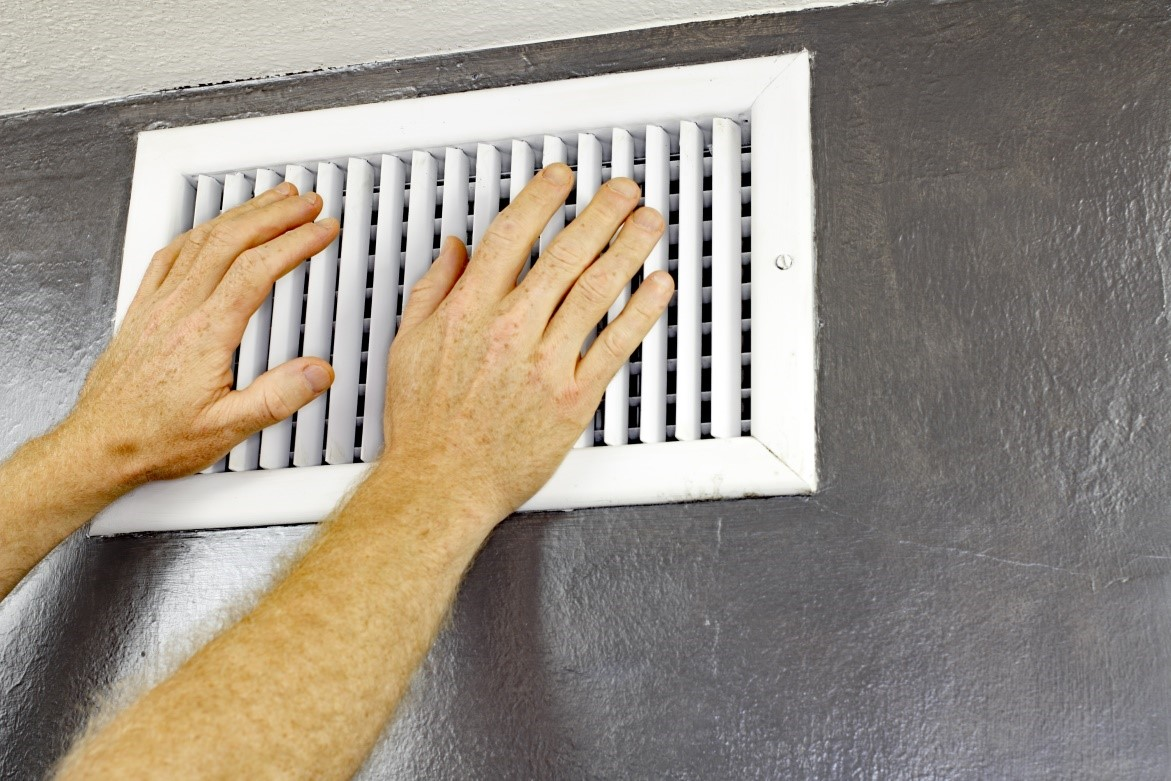 Technician trying to remove air conditioning vent from the wall