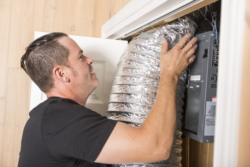 Technician inspecting air conditioning ducts
